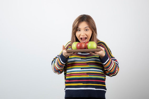 A young cute woman model holding a wooden plate with colorful fresh apples .