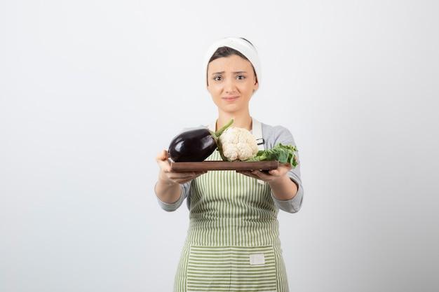 Una giovane modella carina che tiene in mano un piatto di legno con melanzane e cavolfiori