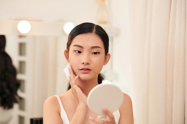 若いかわいい女性が化粧を落とし、鏡を見ながらコットンパッドで顔を掃除する