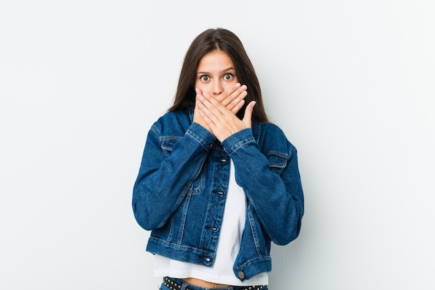 Young cute woman shocked covering mouth with hands.