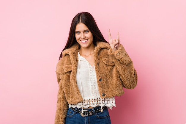 Young cute woman showing a horns gesture as a revolution concept.