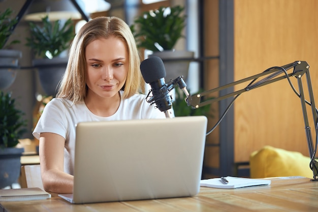Young cute woman sitting at table and working in laptop