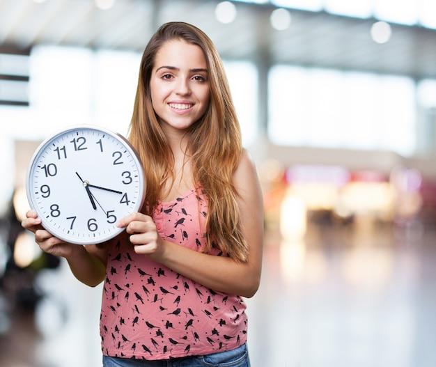 Молодая симпатичная женщина улыбается и проведение часы на белом