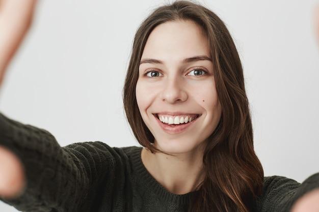 Молодая милая женщина улыбается, принимая селфи на камеру или смартфон