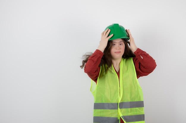 조끼에 서 있고 충돌 헬멧을 쓰고 젊은 귀여운 여자.