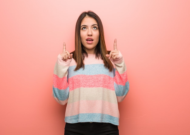 Young cute woman surprised pointing up to show something