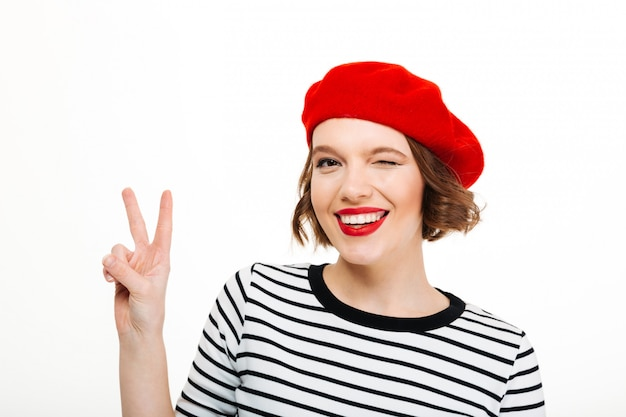 Young cute woman winking and showing peace gesture.