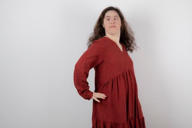 立ってポーズをとってダウン症の若いかわいい女性。