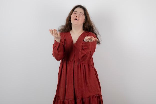 서서 포즈를 취하는 다운 증후군을 가진 젊은 귀여운 여자.