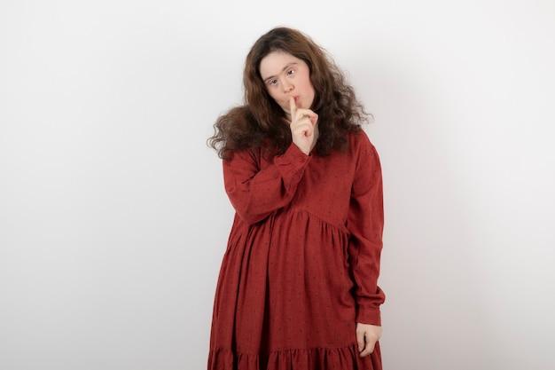 다운 증후군이 있는 젊은 귀여운 여성이 서서 침묵하는 신호를 보여줍니다.