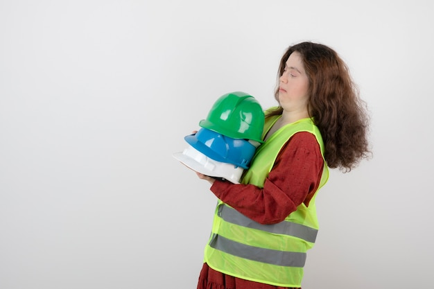 다운 증후군이 있는 젊은 귀여운 여성이 조끼를 입고 충돌 헬멧을 들고 있습니다.