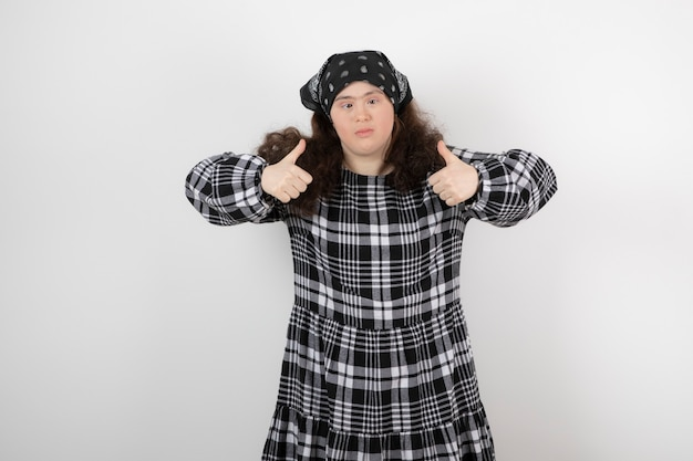 Young cute woman with down syndrome standing and showing thumbs up .