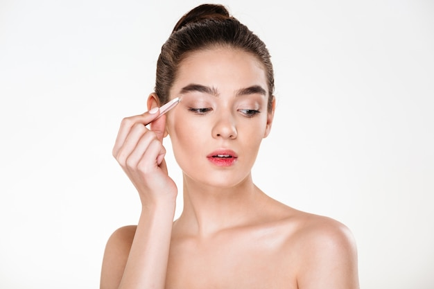 Young cute woman with soft skin plucking eyebrows with tweezers