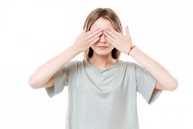 Young cute young woman covering eyes with two hands
