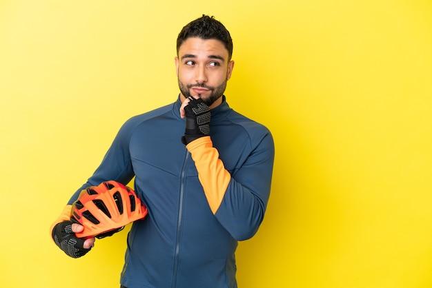 노란색 배경에 고립되어 올려다보는 젊은 자전거 타는 아랍 남자
