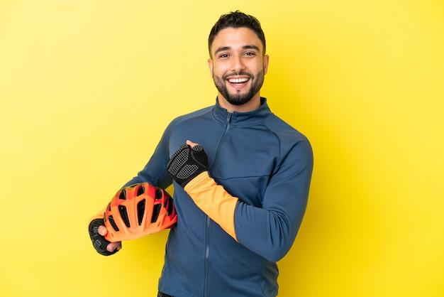 승리를 축하하는 노란색 배경에 고립 된 젊은 사이클리스트 아랍 남자