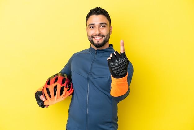 来るジェスチャーをしている黄色の背景に分離された若いサイクリストアラブ人