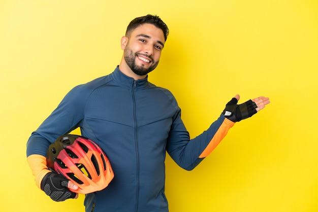 Молодой велосипедист арабский мужчина изолирован на желтом фоне, протягивая руки в сторону для приглашения приехать