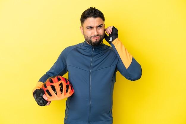 Молодой велосипедист арабский мужчина изолирован на желтом фоне разочарован и закрывает уши