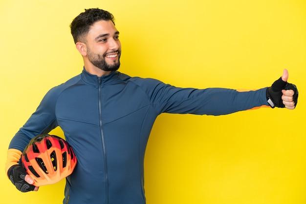 Молодой велосипедист арабский мужчина изолирован на желтом фоне, показывая большой палец вверх жест