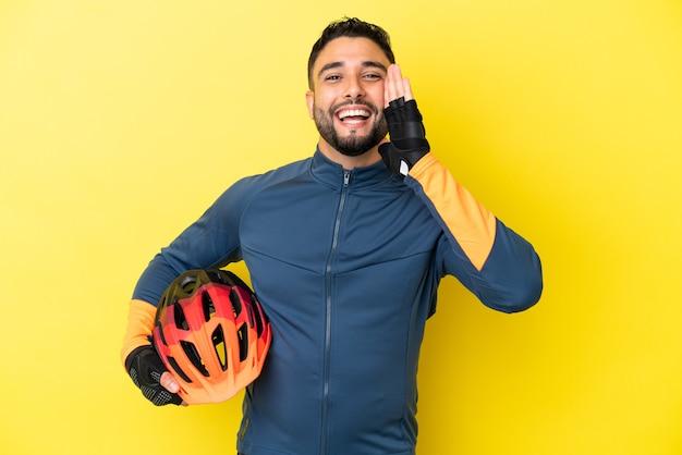 노란색 배경에 격리된 젊은 자전거 타는 아랍 남자가 입을 크게 벌리고 소리를 지릅니다.