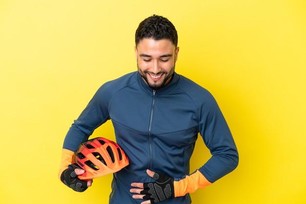 Молодой велосипедист арабский человек, изолированные на желтом фоне, много улыбаясь