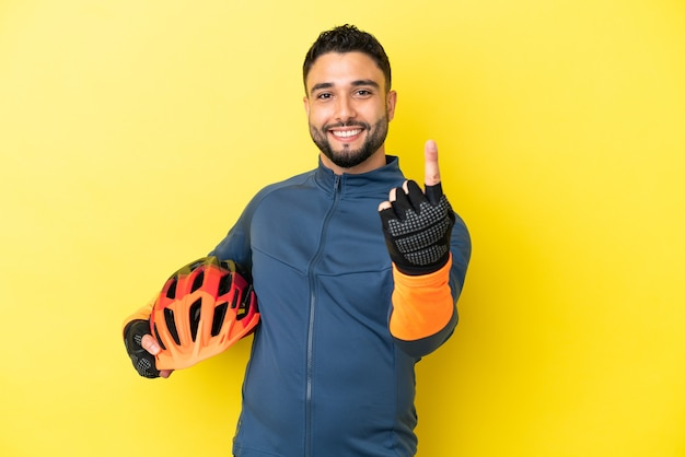 Young cyclist arab man isolated on yellow background doing coming gesture