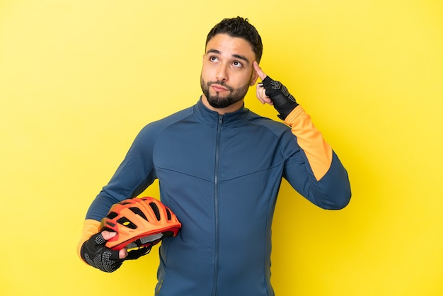Young cyclist arab man isolated on yellow background having doubts and thinking