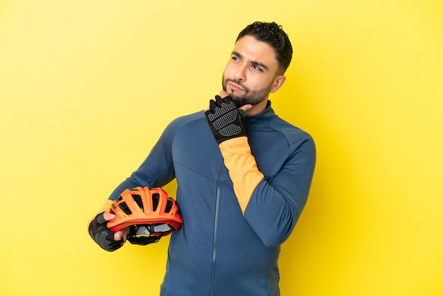 Young cyclist arab man isolated on yellow background having doubts