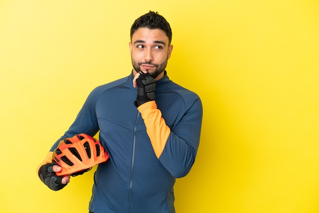 Young cyclist arab man isolated on yellow background and looking up
