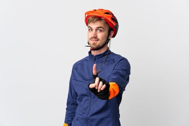 指を見せて持ち上げて白い背景で隔離の若いサイクリスト金髪男