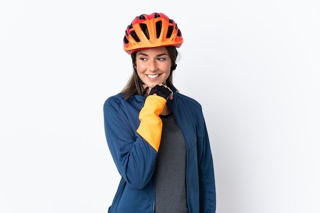 Бразильская девушка молодой велосипедист, изолированные на белом фоне, глядя в сторону и улыбаясь