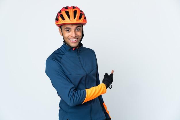Молодой велосипедист бразильский мужчина изолирован на белой стене, указывая назад