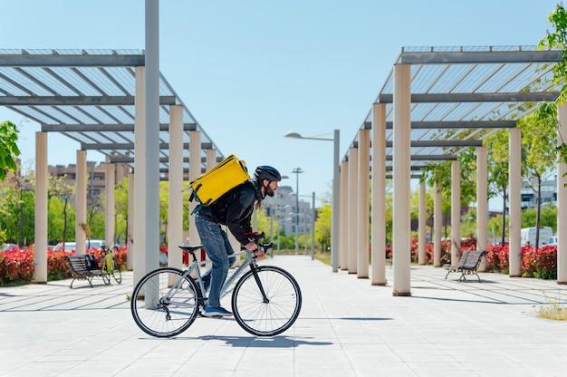 Молодой велосипедист, доставляющий фаст-фуд