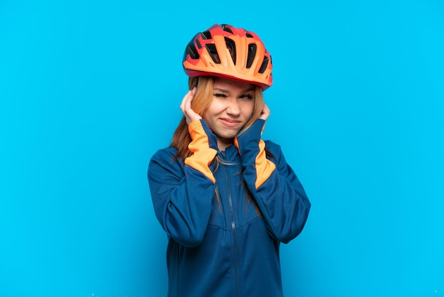 Young cyclist girl isolated on blue background frustrated and covering ears