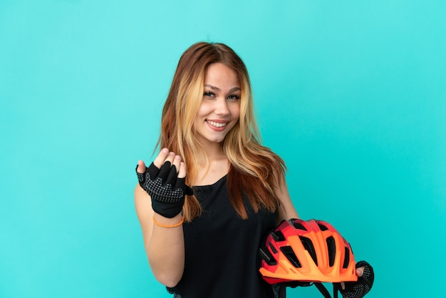 Young cyclist girl over isolated blue background inviting to come with hand. happy that you came