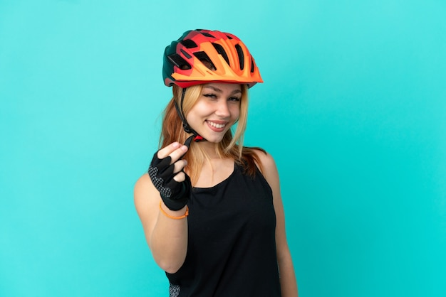 Young cyclist girl over isolated blue background making money gesture