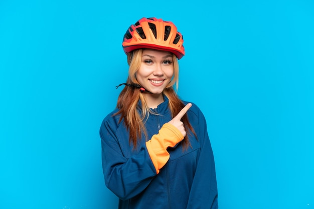 Young cyclist girl isolated on blue background pointing to the side to present a product