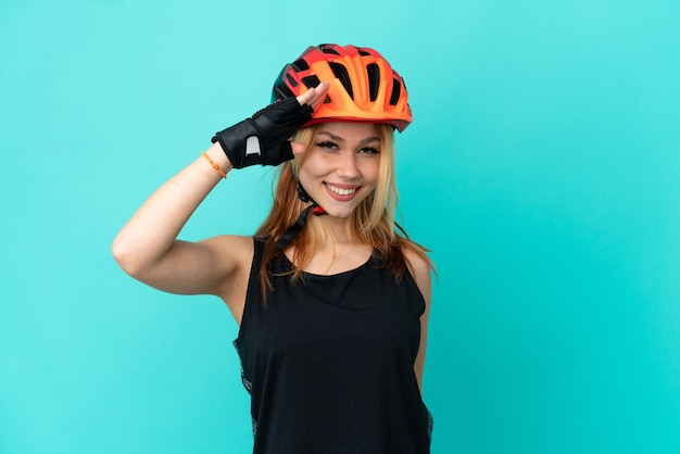 Young cyclist girl over isolated blue background saluting with hand with happy expression