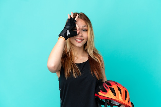 Young cyclist girl over isolated blue background showing ok sign with fingers