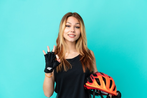 Young cyclist girl over isolated blue background showing ok sign with two hands