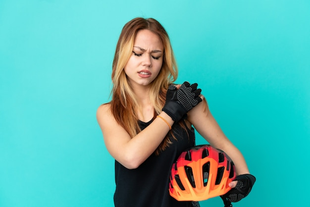 Young cyclist girl over isolated blue background suffering from pain in shoulder for having made an effort