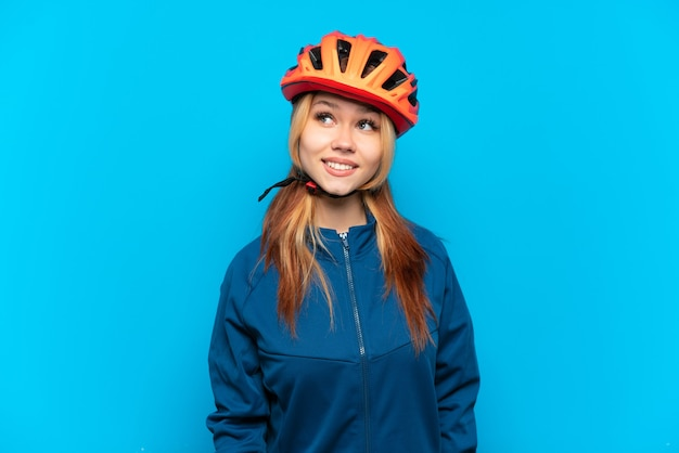 Young cyclist girl isolated on blue background thinking an idea while looking up