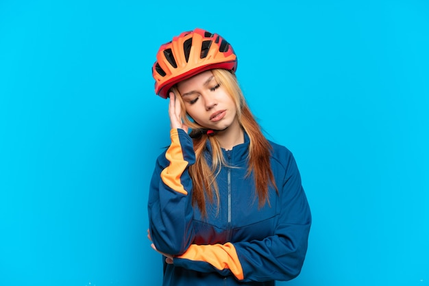 Young cyclist girl isolated on blue background with headache