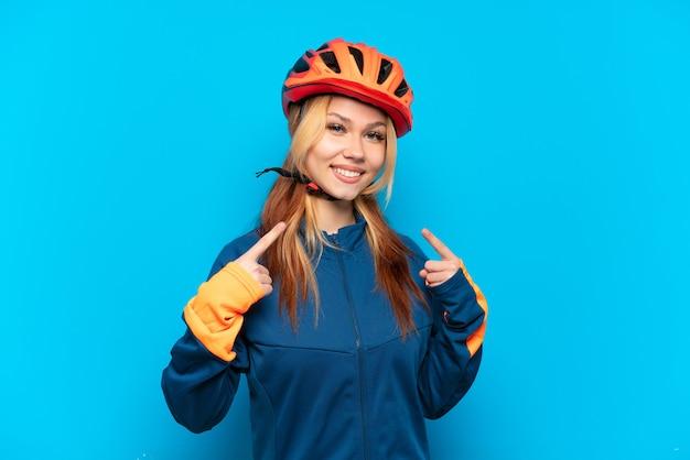 親指を立てるジェスチャーを与える分離された若いサイクリストの女の子