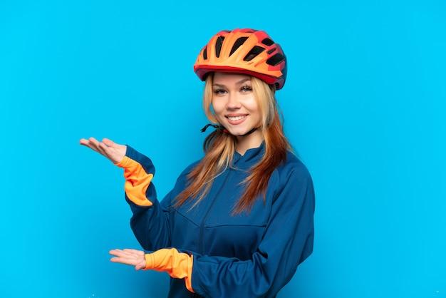 파란색 배경에 고립 된 젊은 자전거 타는 소녀는 올 초대를 위해 손을 옆으로 확장
