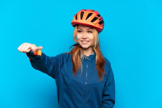Молодая велосипедистка изолирована на синем фоне, показывая жест рукой вверх