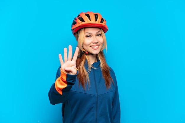 Молодая велосипедистка изолирована на синем фоне счастлива и считает четыре пальцами