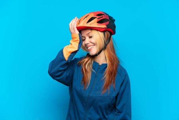 青い背景で隔離の若いサイクリストの女の子は何かを実現し、解決策を意図しています