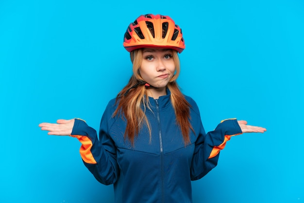 Молодая велосипедистка изолирована на синем фоне, сомневаясь, поднимая руки